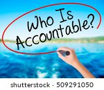 Small photo of Woman Hand Writing Who Is Accountable? on blank transparent board with a marker isolated over water background. Business concept. Stock Photo