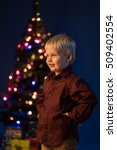 Small photo of Multicolor spruce with decorations and lights bokeh. Child and gifts under the multicolour Christmas tree. Little boy and adornment on the trees