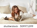 Stock photo pets comfort rest and people concept happy young woman with cat lying in bed at home 509971399