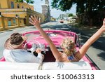 Small photo of Rear view of happy friends enjoying in the convertible car drive through Havana