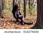 Small photo of Feshionable woman siting on colorfull leaves in autumn forest, looking at sun, wearing vintage sunglesses abd boots.
