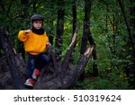 a boy is sitting on the fallen... | Shutterstock . vector #510319624