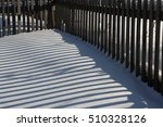 fence shadow on snow accumulated deck