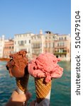 Small photo of Holding traditional italian ice cream called Gelato in the waffle cone on Venice canal background in Italy.