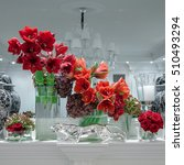 Small photo of red flowers amaryllis in glass vases with iron leopard. Luxury interiors