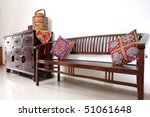A teakwood Balinese-style batavia bench next to a teakwood console table. - stock photo