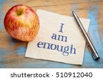Small photo of I am enough positive affirmation - handwriting on a napkin with a fresh apple
