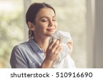 Stock photo beautiful young woman is smelling clean clothes and smiling while doing laundry at home 510916690