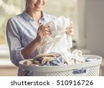 Stock photo cropped image of beautiful young woman is smiling while doing laundry at home 510916726