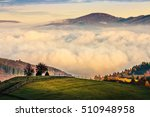 cold morning fog with golden hot sunrise over rural area in mountain. fence and trees with colorful foliage on the green meadow  - stock photo