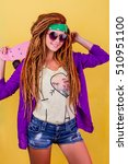 Small photo of Pretty girl with dreadlocks and green do-rag holding rose skateboard and smiling