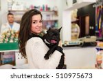 Stock photo beautiful brunette woman with her french bulldog puppy in pet shop selective focus on dog 510975673