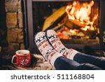 feet in woollen socks by the... | Shutterstock . vector #511168804