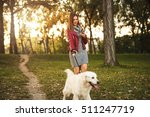 Stock photo attractive girl texting on the phone and walking the dog 511247719
