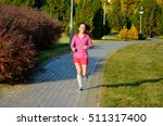 woman running in autumn park ... | Shutterstock . vector #511317400