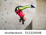 Small photo of Active happy woman hanging on trope in the artificial climbing wall, doing split