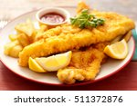 two pieces of battered fish on... | Shutterstock . vector #511372876