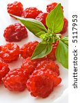 Raspberries with green basil leaves on white plate - stock photo