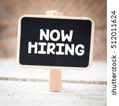 Small photo of Now hiring/Now hiring handwritten on framed blackboard