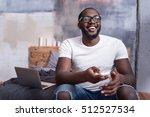 delighted man watching tv in... | Shutterstock . vector #512527534
