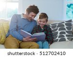 father and son reading a book... | Shutterstock . vector #512702410