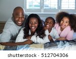 happy family lying on bed at... | Shutterstock . vector #512704306