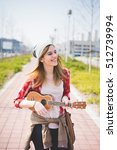 Small photo of young beautiful blonde hipster woman in the city with ukulele