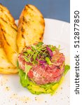 Small photo of Ahi tuna tartare stacked with avocado, arugula, topped with micro greens, served with grilled crostini bread