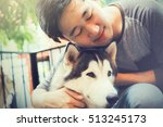 Stock photo young asian male dog owner hugging and embracing the husky siberian dog pet with love and care 513245173