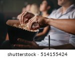 Close up shot of young people eating popcorn in movie theater, focus on hands.