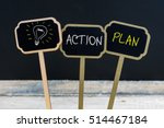 Small photo of Concept message ACTION PLAN and light bulb as symbol for idea written with chalk on wooden mini blackboard labels, defocused chalkboard and wood table in background