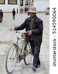 Small photo of LHASA, TIBET - 7 MAY 2014: A man walks with his bicycle in the Tibetan capital, Lhasa. Bicycles are a popular and affordable method of transport in Tibet. Editorial.