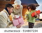 Small photo of afro American parents give their little daughter a Christmas presents, happy girl looking at gifts
