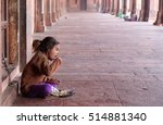 Small photo of FATEHPUR SIKRI, INDIA - FEBRUARY 15: A poor girl eating in Fatehpur Sikri complex, Uttar Pradesh, India on February 15, 2016.