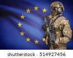 Soldier in helmet holding machine gun with national flag on background - European Union