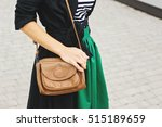 Small photo of Fashion woman in striped T-shirt and green jacket. Fashionable woman in dress and coat with little leather brown handbag on the shoulder. Trendy clothes, street vogue look