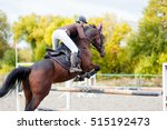 Stock photo young rider girl on horse jumping over obstacle on her course in competition 515192473