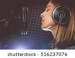Music Passionate Singer and the Microphone. Young Caucasian Singer in Her 20s Recording Album in the Professional Studio. Singing with Passion. - stock photo