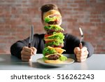 man eating huge burger at table | Shutterstock . vector #516262243