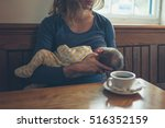 a young mother is breastfeeding ... | Shutterstock . vector #516352159