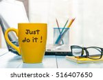 Stock photo lettering of inspirational quote just do it on yellow morning coffee or other hot drink cup at home 516407650