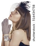 Small photo of Portrait of a stylish pious beautiful young lady wearing gloves and black feather light hat with net veil, looking up and praying with clasped hands over white background.
