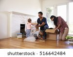 family unpacking boxes in new... | Shutterstock . vector #516642484