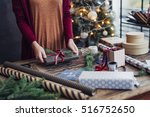 woman tying ribbon on christmas ... | Shutterstock . vector #516752650