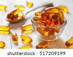 fish oil capsules on wooden... | Shutterstock . vector #517209199