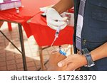Small photo of a medical officer administering an injection to a patient's hand. outdoor.