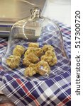 Small photo of White Alba truffles under bell jar on blue checkered tablecloth, Italy