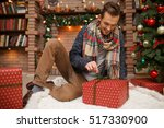 smiling man opening christmas... | Shutterstock . vector #517330900