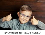 a child with glasses gives a... | Shutterstock . vector #517676560