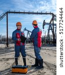 Small photo of Two workers in the oilfield. Pump jack, pipeline and wellhead background. Oil and gas concept.